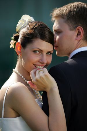 A beautiful bride looking over the shoulder of her new husband photo