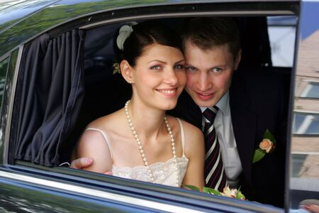 seem: A newly married man and woman seem here looking out of the window of their wedding car limousine after the wedding ceremony