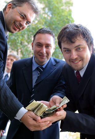 A portrait of three businessmen all holding the same pile of dollar bills in their hands Stock Photo - 2209999