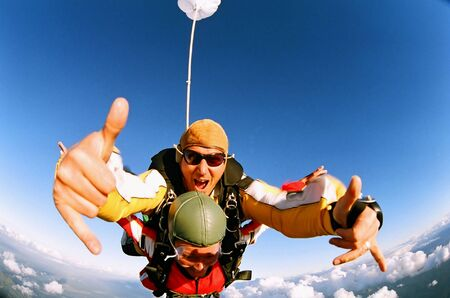 rapture: A tandem skydiver giving the thumbs up sign
