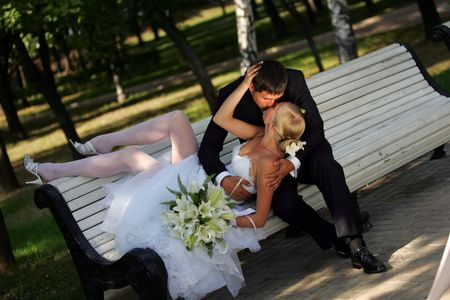 Portrait of a beautiful bride on her wedding day. She is reclining to kiss her new husband on a park bench.