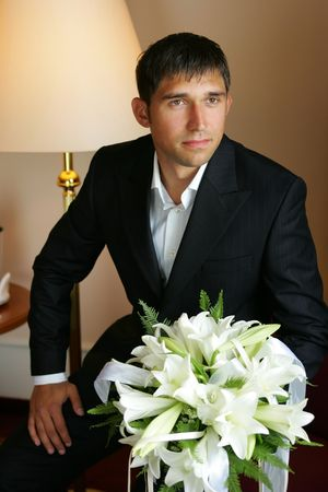 A smiling groom in a suit on his wedding day. He is sat in his hotel room nervously holding a bouquet of flowers. Stock Photo - 2196464