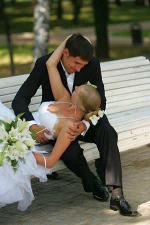 banc parc: Portrait d'une belle �pouse pour son mariage. Elle est inclinable pour baiser son nouveau mari sur un banc de parc.  Banque d'images