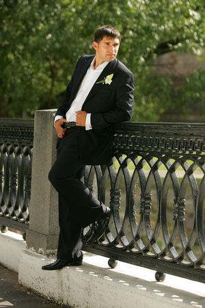 A smiling groom in a suit on his wedding day. He is stood on a bridge and relaxing. Stock Photo - 2196471