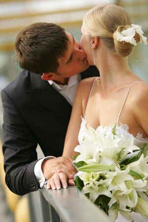 a newly married couple: Portrait of a newly married couple kissing on a bridge