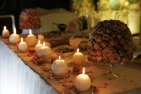 marrage: Some burning candles burning on a table at a wedding reception.