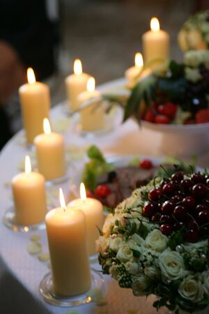Some burning candles burning on a table at a wedding reception. photo