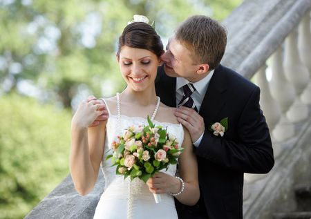 Portrait of a bride in a beautiful white traditional wedding dress. Her new husband is whispering in her ear, Stock Photo - 2223324