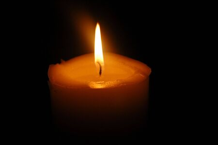 A portrait of an isloated burning candle in the dark photo
