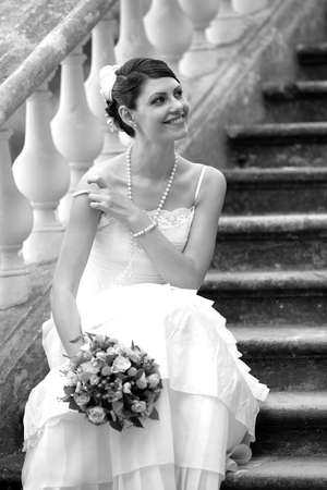 A portrait of a beautiful woman in a traditional white wedding dress with a bouquet of flowers.