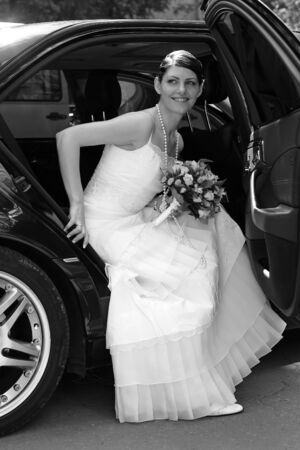A portrait of a beautiful bride wearing a traditional white wedding dress. She is getting out of a black wedding car limousine. photo