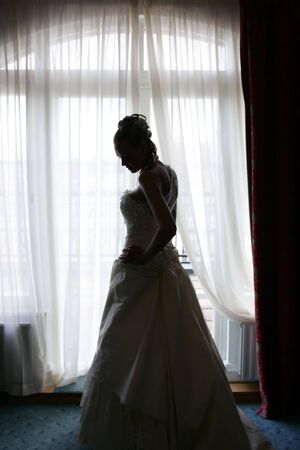 A portrait of a newly married bride stood by a hotel bedroom windowin silhouette. photo