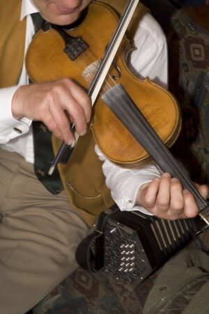 A close up portrait of an Irish Folk Fiddle player pictured playing in a pub in Dublin in Ireland.