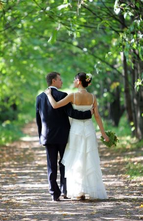A portrait of a bride in a traditional white wedding dress. She is walking down a country lane with her new husband arm in arm. photo