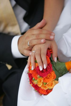 show off: A newlywed couple holding hands to show off their wedding rings