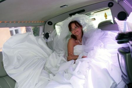A portrait of a beautiful bride in a wedding car limousine. She is sat on the back seat smiling. Stock Photo - 2421070