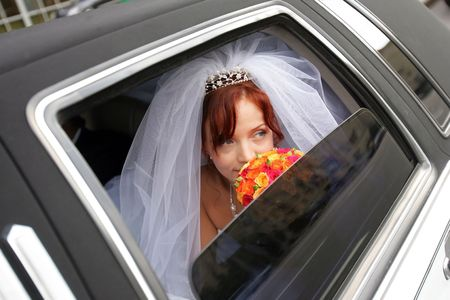 A portrait of a beautiful bride in a wedding car limousine. She is holding a bouquet of flowers and looking out of an open window. Stock Photo - 2421074