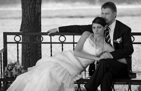 A portrait of a newly married couple pictured cuddling on a park bench photo