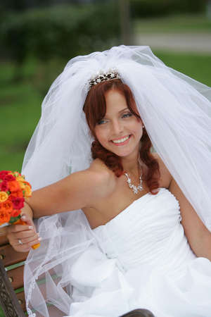 A portrait of a beautiful bride in a traditional white wedding dress pictured sat on a bench holding a bouquet of flowers and smiling. Stock Photo - 2471053