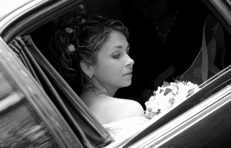 A portrait of a bride in a traditional dress with a bouquet of flowers looking out of the window of her wedding car limousine. photo