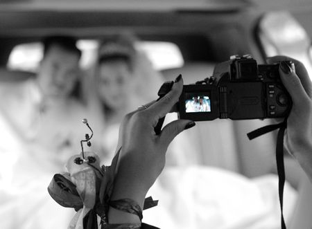 A portrait of a bride and groom travelling in their wedding car limousine after being married. In the foreground someonw is videoing them together. The picture is in black and white, with the image on the video camera being in colour. photo