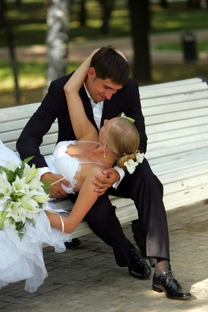 A portrait of a newly married couple sat on a park bench. The groom is leaning down to kiss his bride, who is reclining and holding a bouquet of flowers. Stock Photo - 2471049