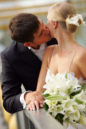 A portrait of a newly married couple kissing each other on their hotel balcony. They are holding hands, and the bride has a wedding bouquet. Stock Photo - 2471060