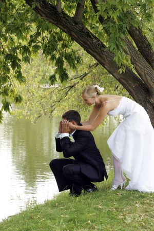 under a tree: A portrait of a newly married couple sat by a lake. The groom is sat under a tree with his hands over his eyes as his new wife creeps up behing him.