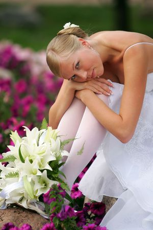 sat: A portrait of a bride in a traditional white wedding dress sat with her head in her hands looking sad. On the floor is a bouquet of flowers.