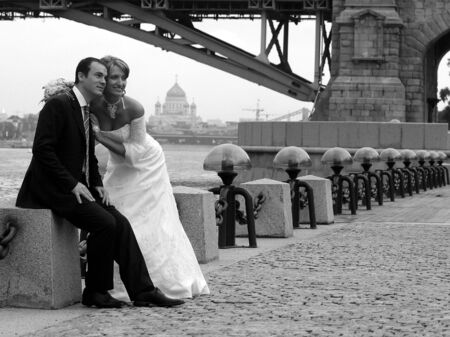 a newly married couple: A portrait of a newly married couple posing underneath a bridge for some photographs after their wedding.