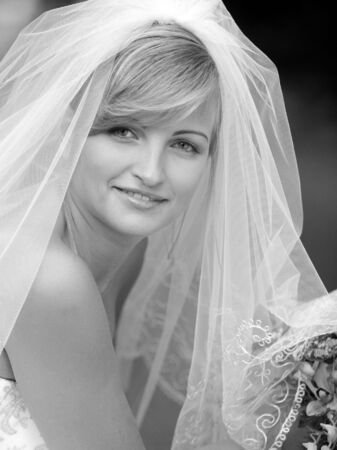 Smiling bride in black and white portrait with bouquet and veil Stock Photo - 2495054