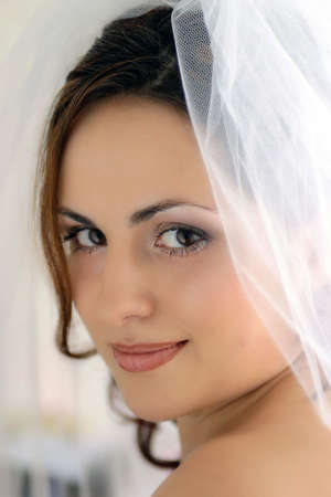 sanctioned: A portrait of a Bride pictured on her wedding day. She is wearing a traditional white wedding dress with a veil, and is seen here smiling at the camera in a half body portrait.rrrrrMarriage is a socially sanctioned union that reproduces the . In all Stock Photo
