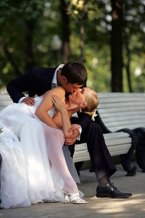 passionately: Newlywed couple in traditional wedding clothes kissing passionately on park bench.