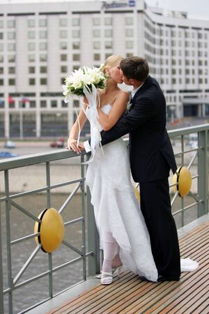 Attractive newlywed couple kissing each other after marriage ceremony. photo