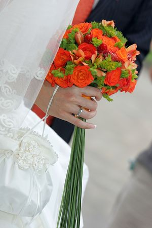 Bride holding a red bouquet of flowers in her hands from\ beneath her wedding dress veil