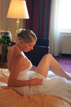 Sexy bride getting undressed on her bed in he hotel room. photo