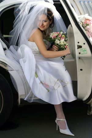 exiting: Smiling bride with bouquet exiting her wedding car limousine. Stock Photo