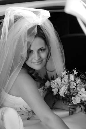 Smiling bride in traditional white wedding dress hetting out of wedding car limousine with bouquet of flowers. photo