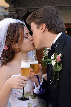 A newly married bride and groom kissing each other and toasting each other with glasses of wine. Stock Photo - 2576558