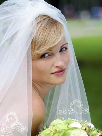 look pleased: A portrait of a bride in a traditional white wedding dress holding a bouquet and smiling. Stock Photo
