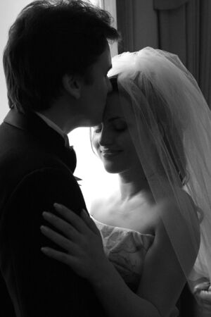 Happy bride and groom in hotel room kissing after wedding
