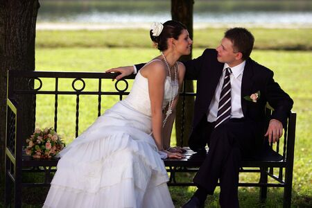 Newlywed couple kissing on park bench after wedding ceremony photo