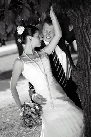 Bride and groom kissing under tree after wedding ceremony. Bride is holding a bouquet Stock Photo - 2612645