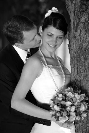 Bride and groom kissing under tree after wedding ceremony. Bride is holding a bouquet