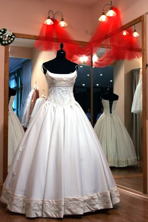 Traditional white wedding dress in shop window, near to changing room.