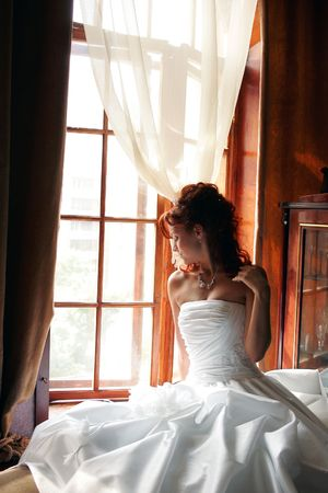 Wedding day bride in traditional white dress in hotel bedroom before marriage ceremony