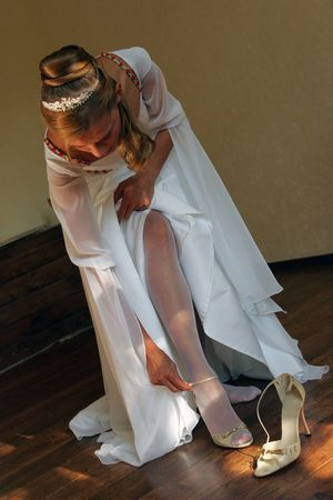 Bride in traditional white wedding dress putting on her wedding shoes Stock Photo - 2624700