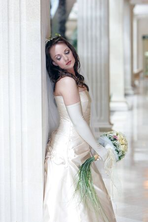 Bride in traditional white wedding dress stood with bouquet photo