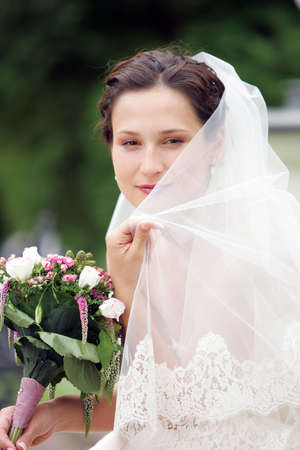 Smiling bride in traditional white wedding dress photo