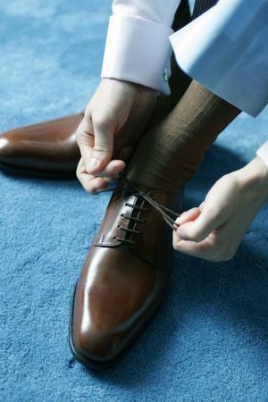 brogues: Man putting on brown leather shoes for work